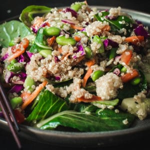 Side view of asian sesame quinoa salad on black plate with chopsticks.