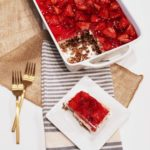 Strawberry Pretzel Salad in white casserole dish with square piece cut out