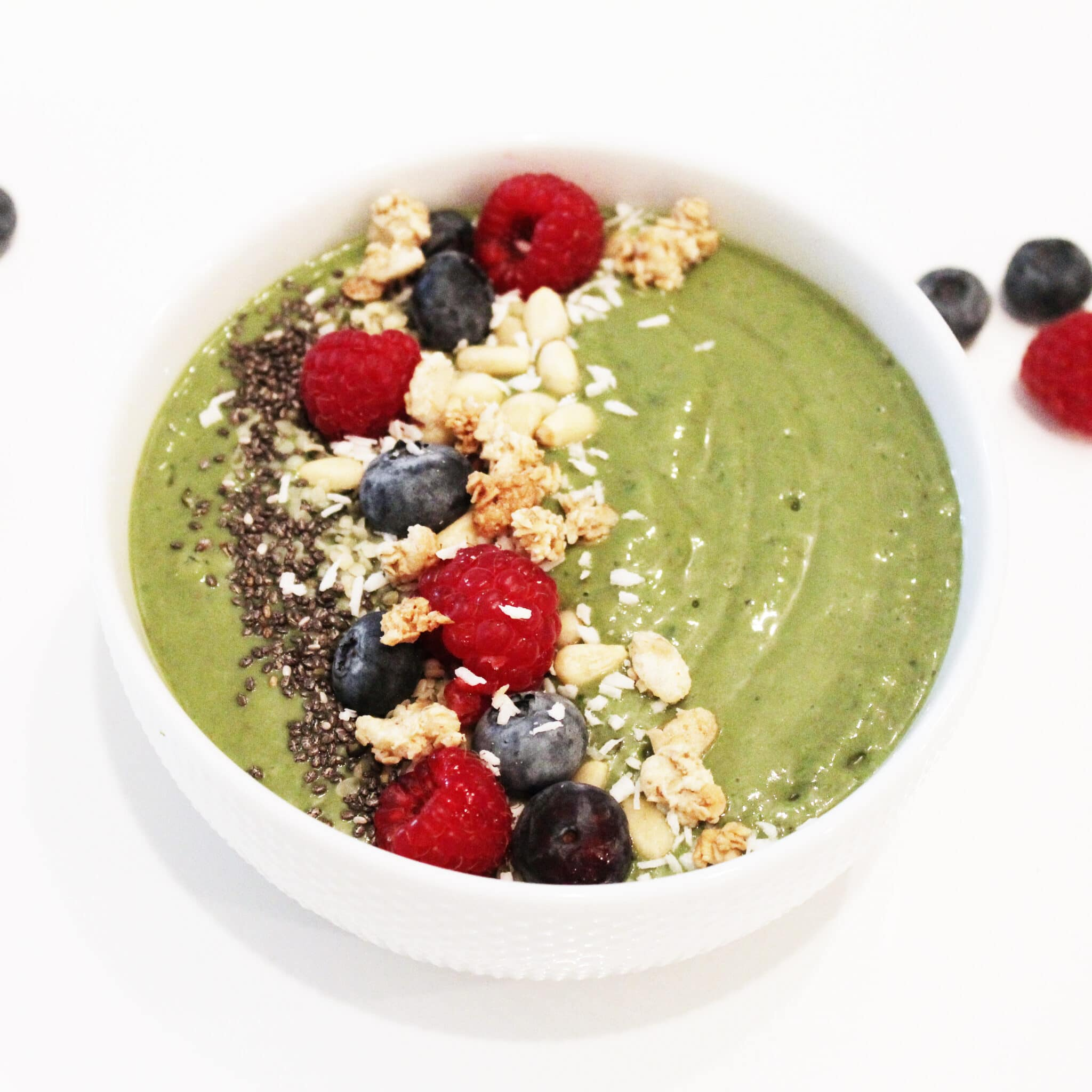 super green smoothie bowl topped with berries, granola, and coconut flakes