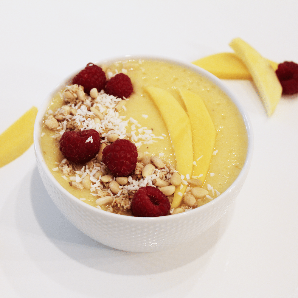 mango smoothie bowl in white bowl topped with berries and coconut