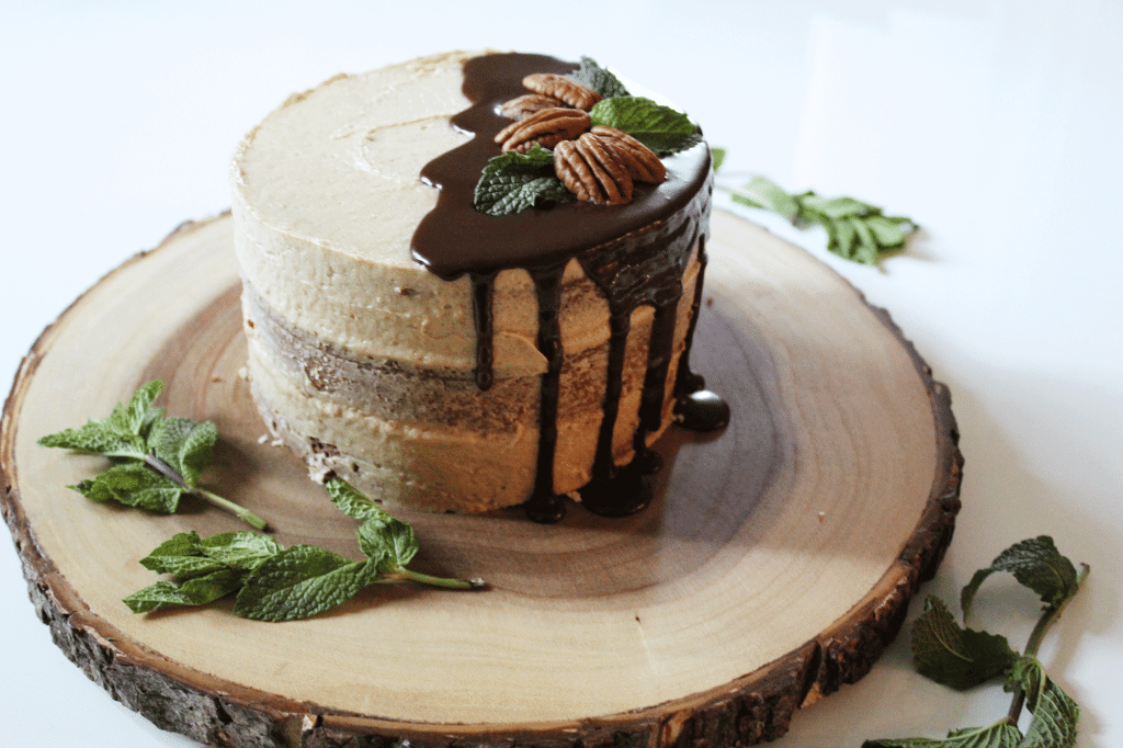 Lightly frosted spice cake with bourbon buttercream and a chocolate ganache dripping on the side topped with pecans and mint leaves.