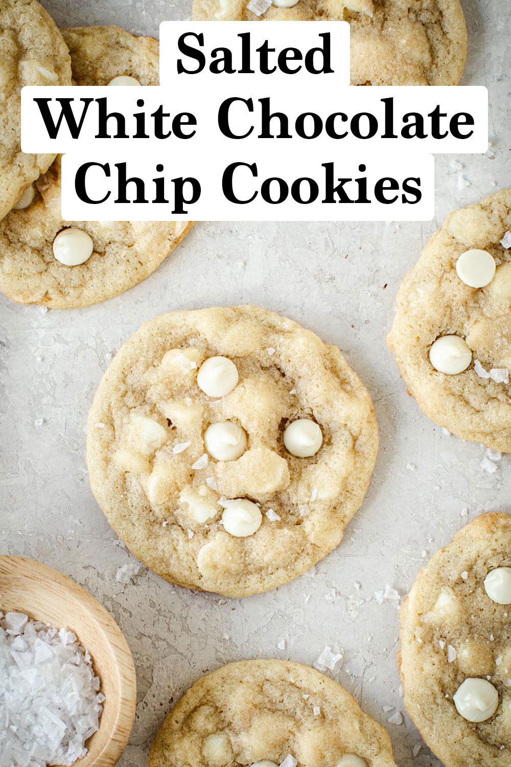 Salted white chocolate chip cookies spread out on white board.
