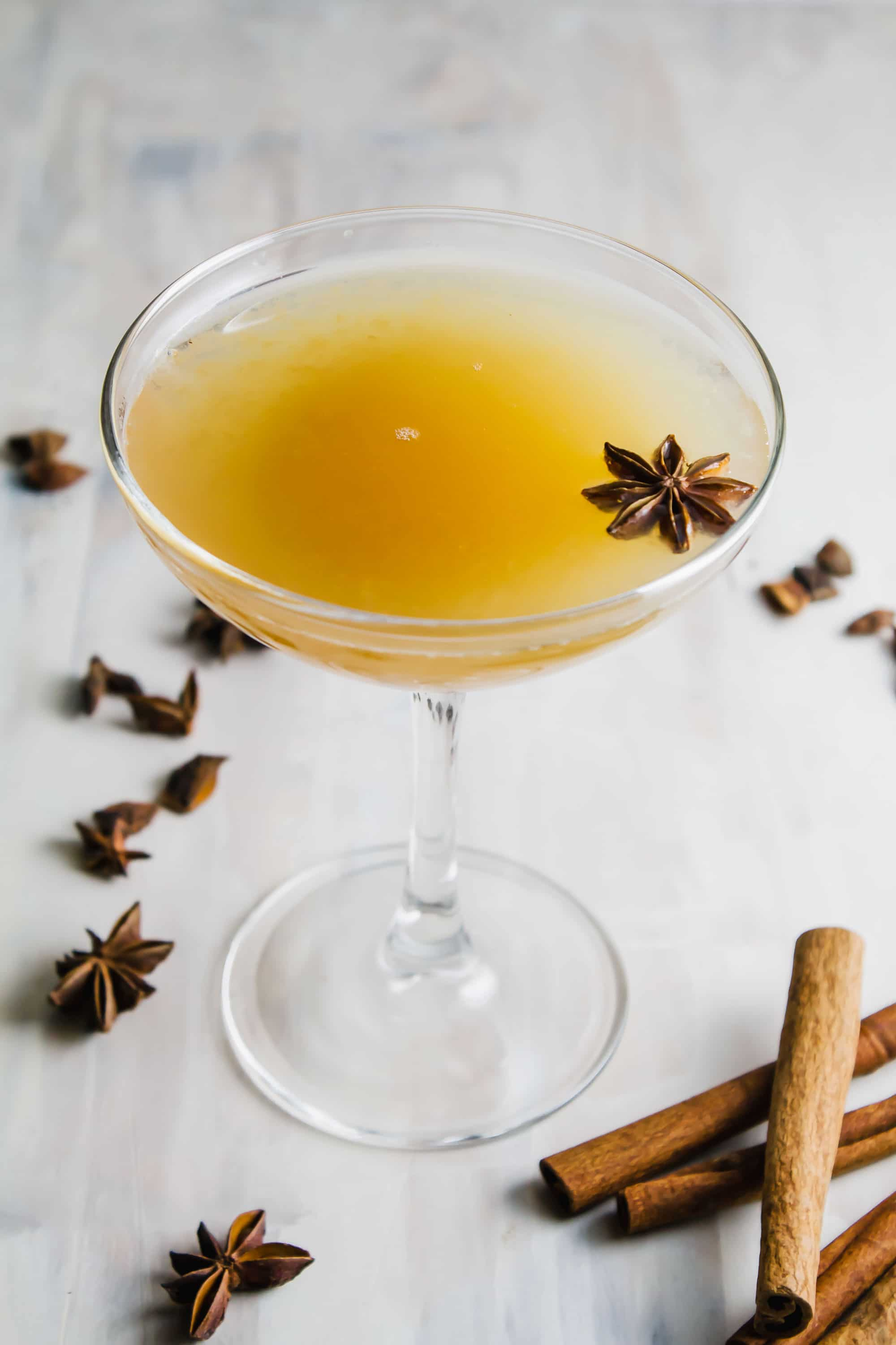 Apple cider hot toddy in a cocktail glass with whole star anise on top.