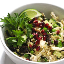 Chicken and quinoa salad in white bowl with lime wedge and parsley.