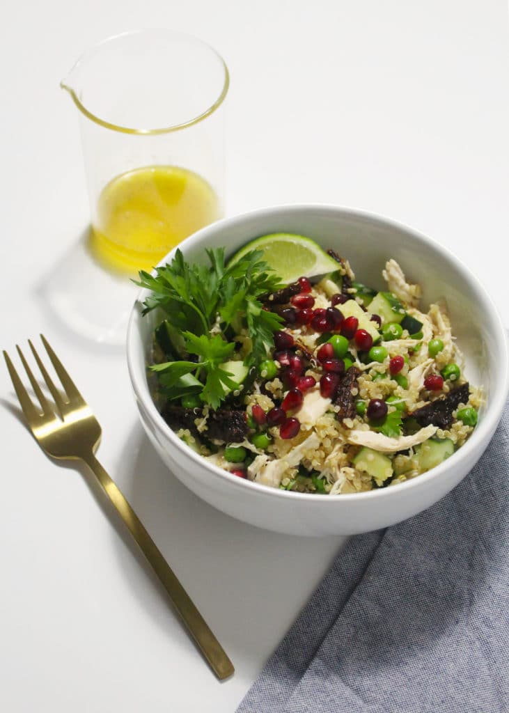 chicken and quinoa salad in white bowl with gold fork