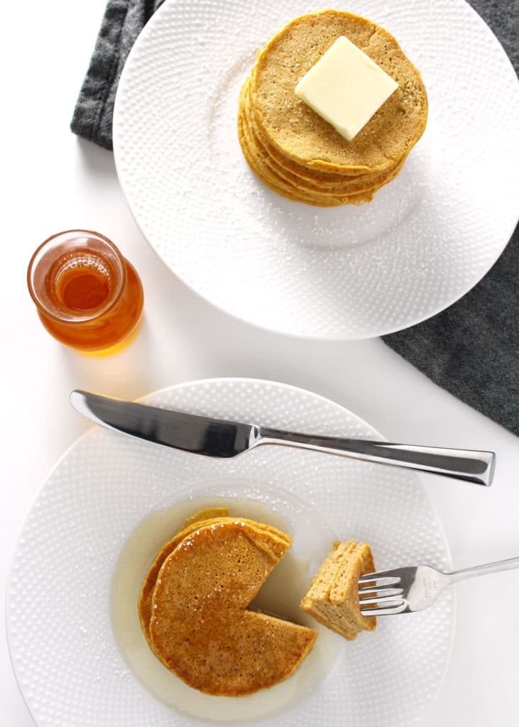 pumpkin pancakes on white plates with silver fork and knife