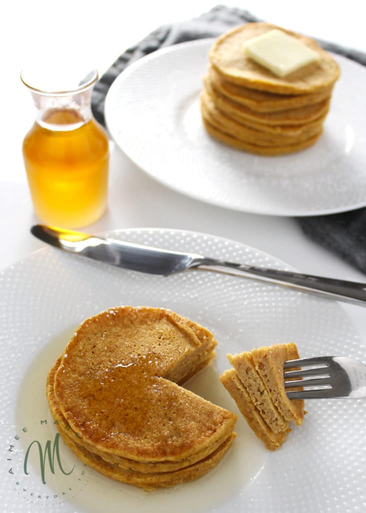 healthy pumpkin pancakes on white plates with slice cut out