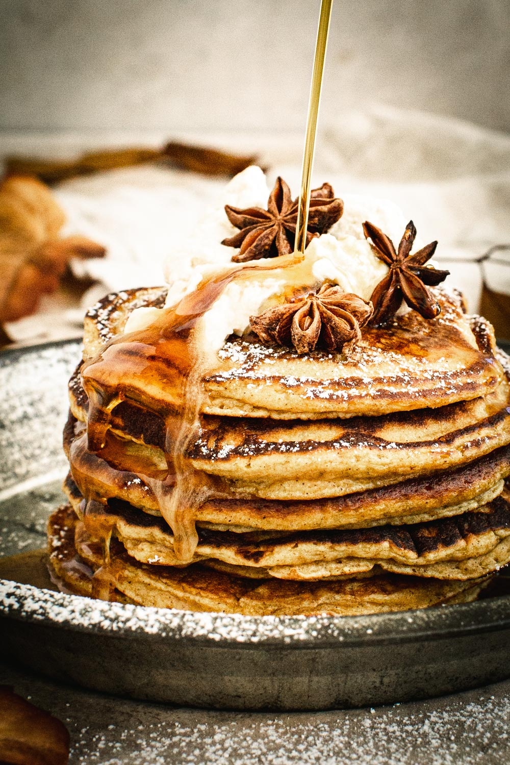 Drizzling syrup on top of pumpkin pancakes with whipped cream and powdered sugar.