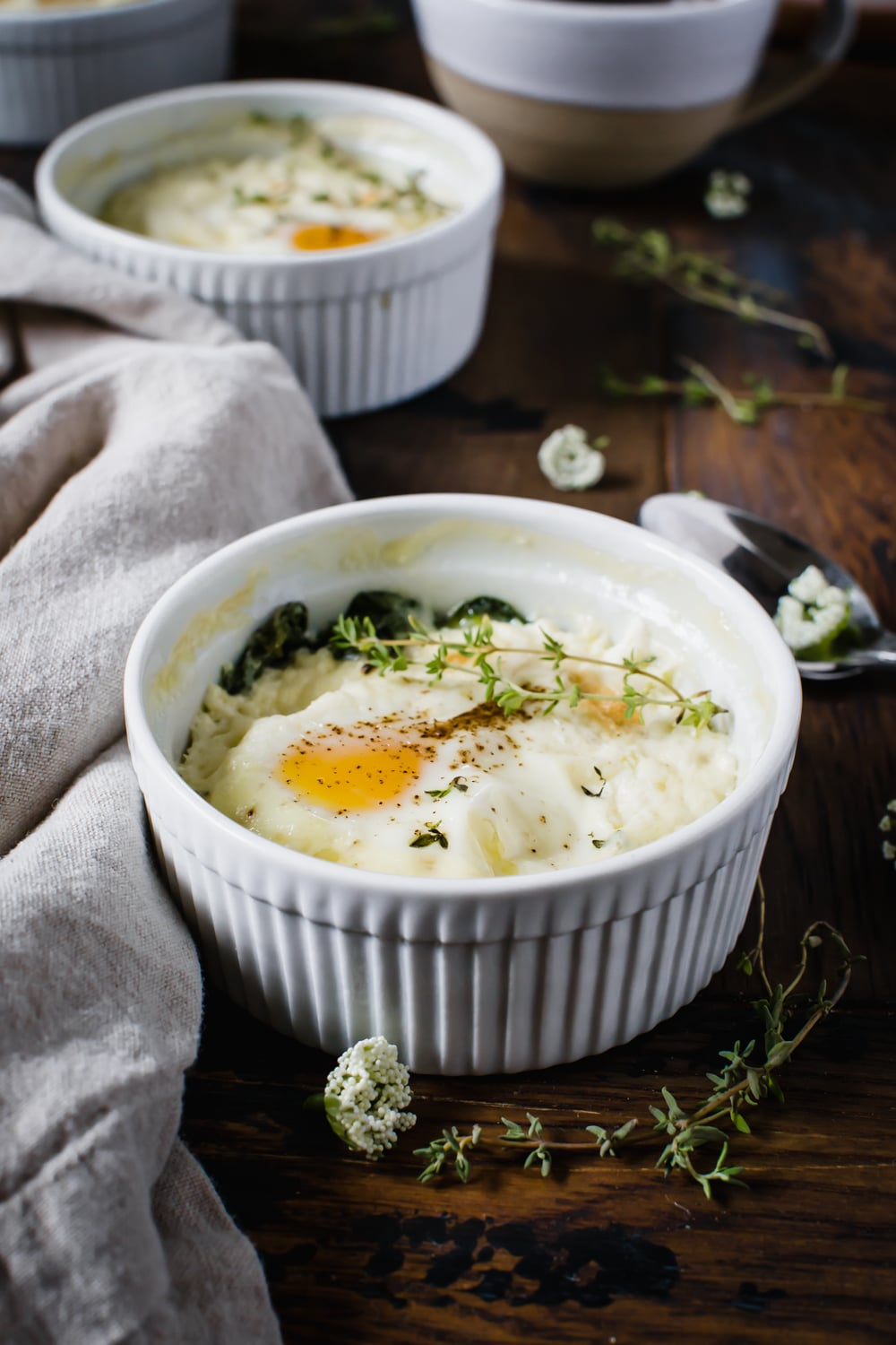 baked eggs with ricotta and thyme in white ramekin next to napkin