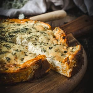 goat cheese and herb quiche with slice cut out on wooden board