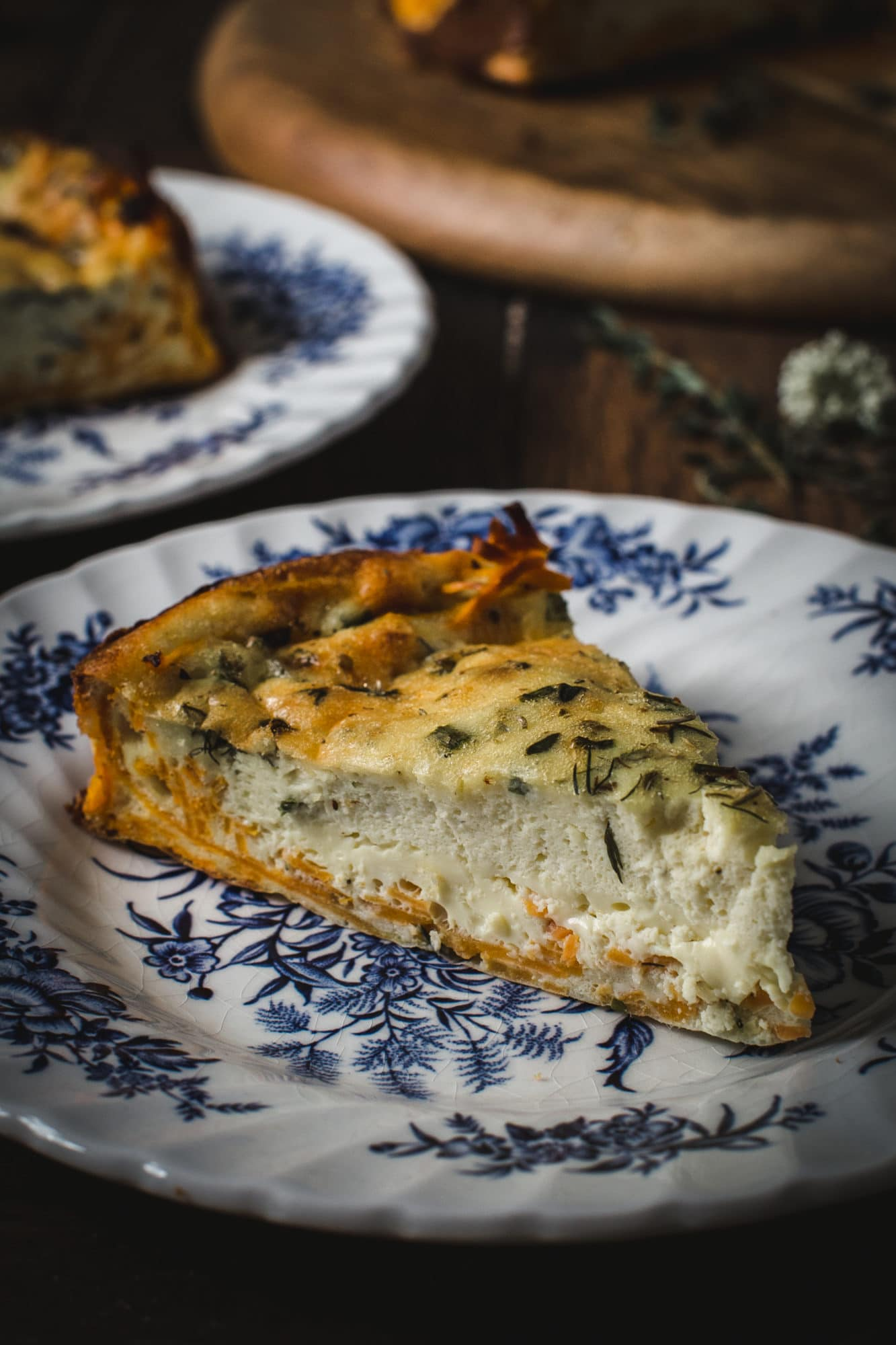 Goat Cheese and Herb Quick with Sweet Potato Crust slice on white china with blue floral