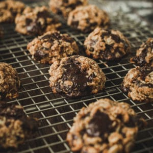 Oatmeal cookies with chocolate chips on wire rack.