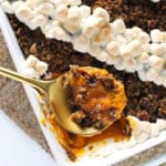 close up scoop of sweet potato casserole on gold serving spoon