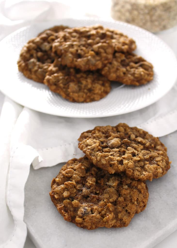 close up of chocolate chip oatmeal cookies with plate full in the background