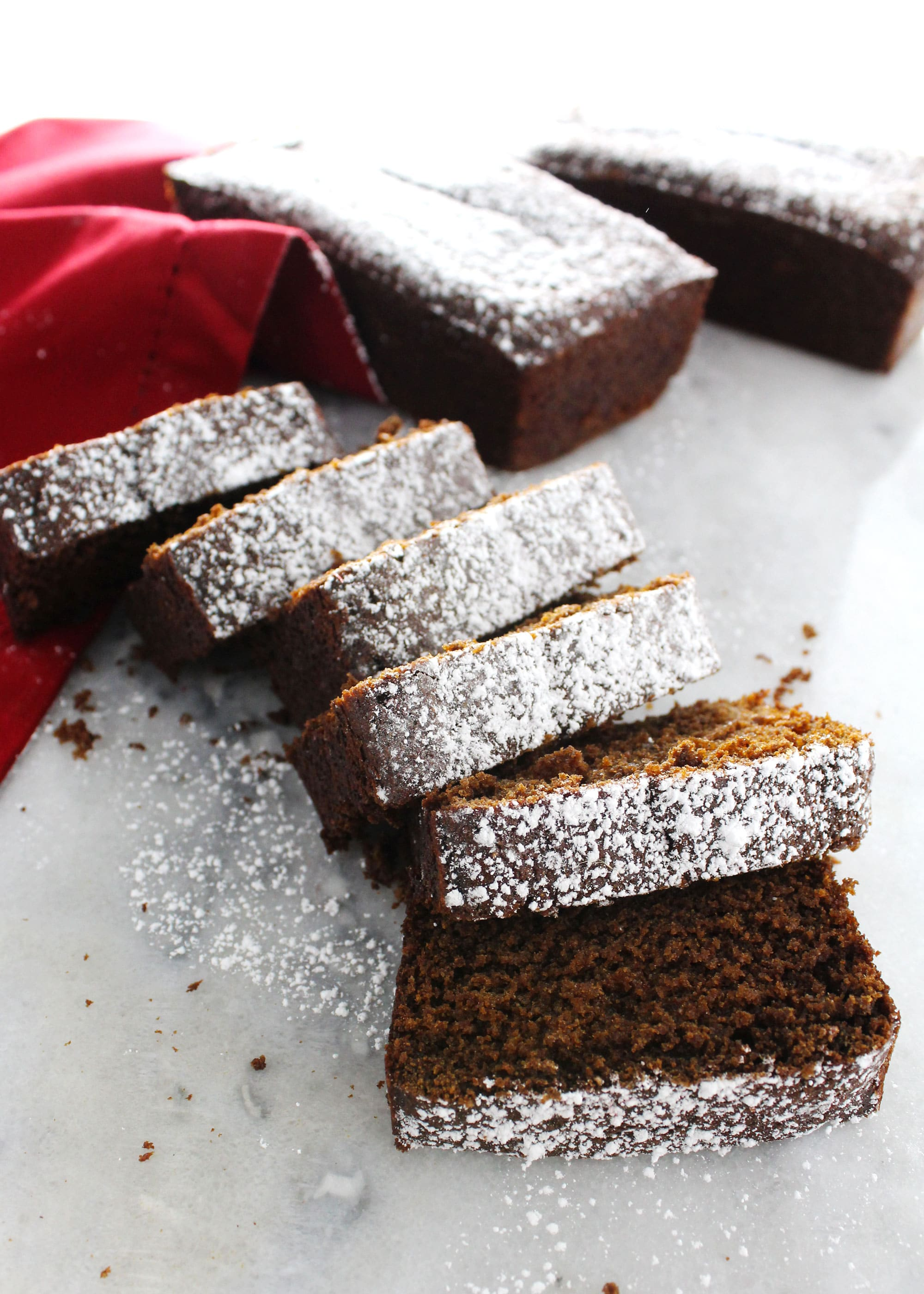 gingerbread loaf sliced and dusted with powdered sugar on a red napkin