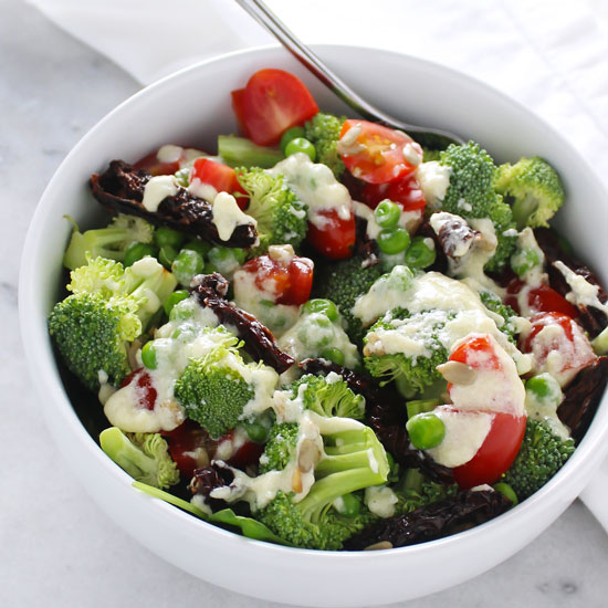 parmesan dressing on broccoli salad in white bowl