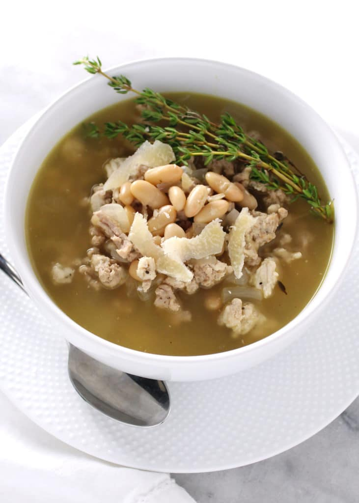 turkey and white bean stew with thyme sprig in white bowl