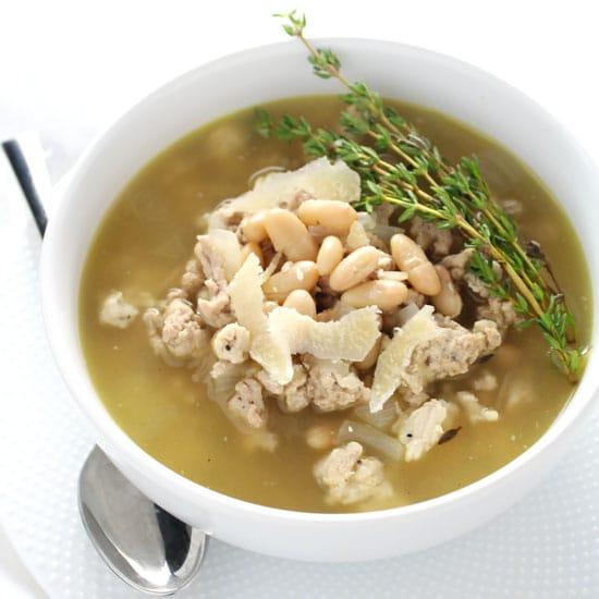 white bean stew in white bowl with silver spoon