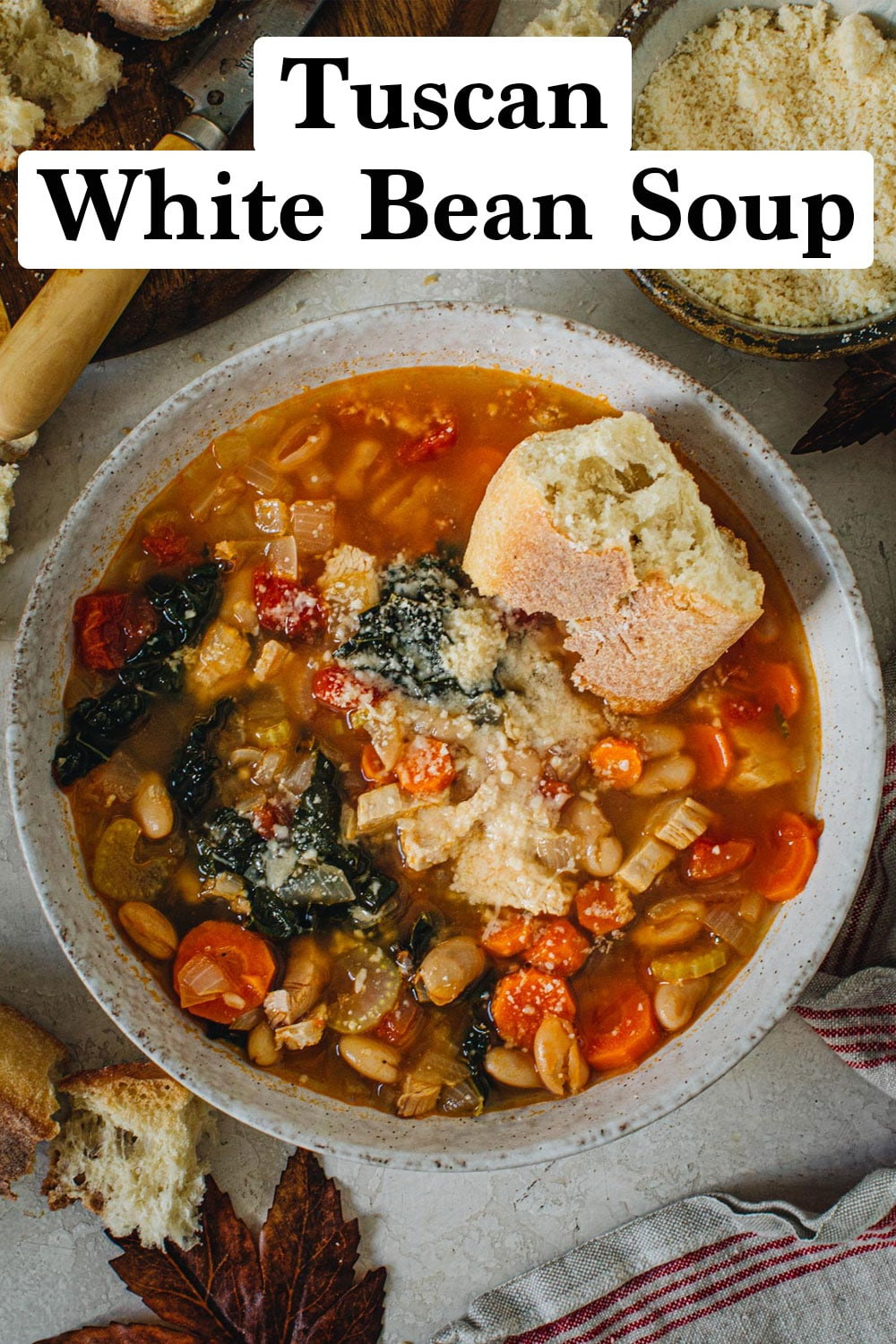 Tuscan white bean soup with crusty bread on top in a bowl.
