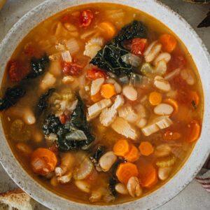 Tuscan white bean soup in a white bowl.