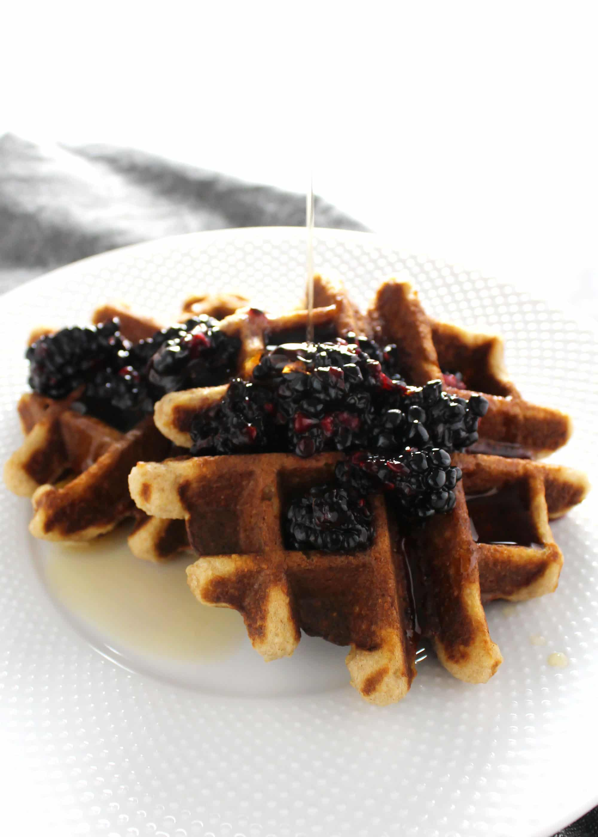 coconut flour waffles topped with blackberry jam on a white plate