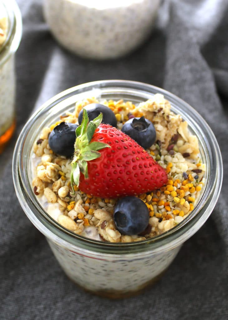 close up of overnight oats topped with bee pollen and blueberries