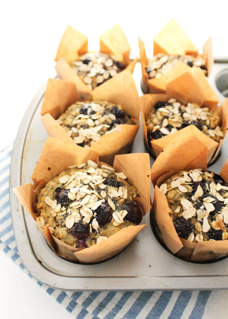 blueberry chia oat muffins in muffin tin with brown liners