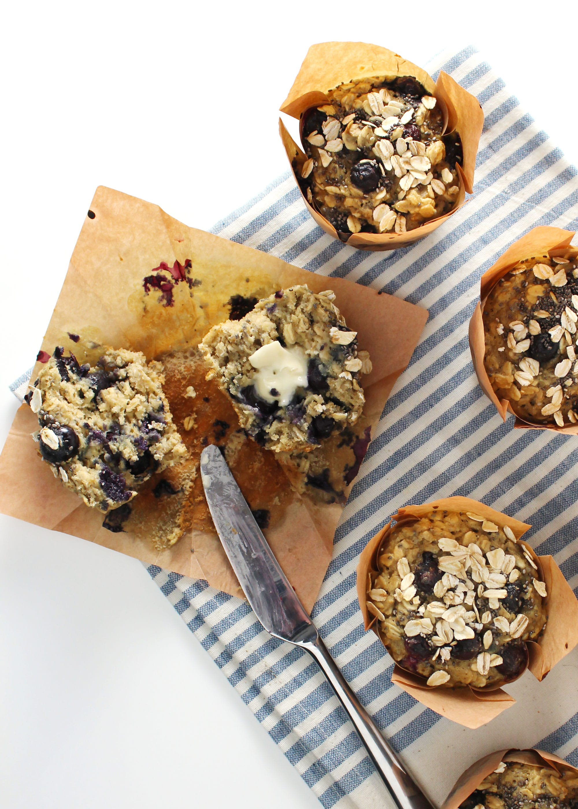 blueberry chia oat muffin sliced in half with butter and silver knife