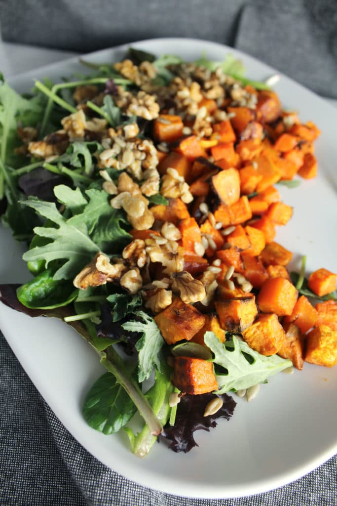 walnut and roasted sweet potato salad on a white tray