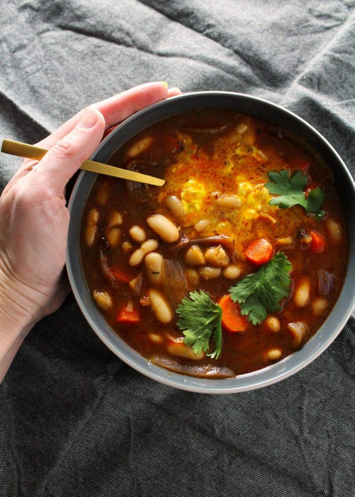 white bean stew birds eye view of bowl with gold spoon