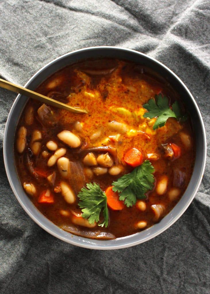 close up of thai white bean stew in gray bowl on gray napkin