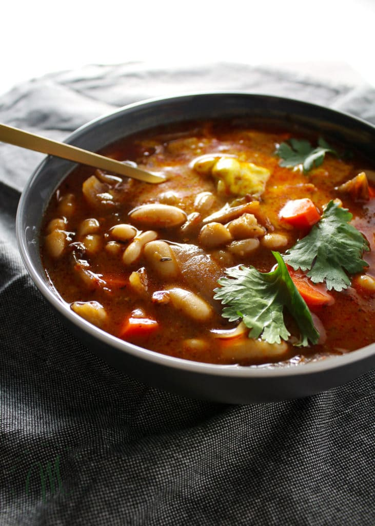 Thai white bean stew with turmeric yogurt in gray bowl with gold spoon
