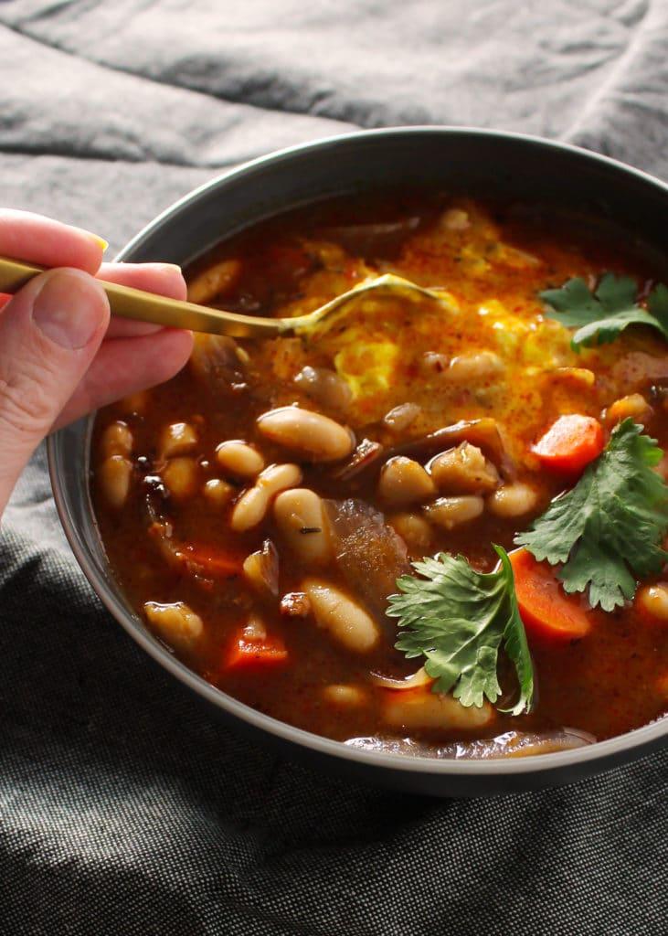 gold spoon stirring white bean stew in gray bowl