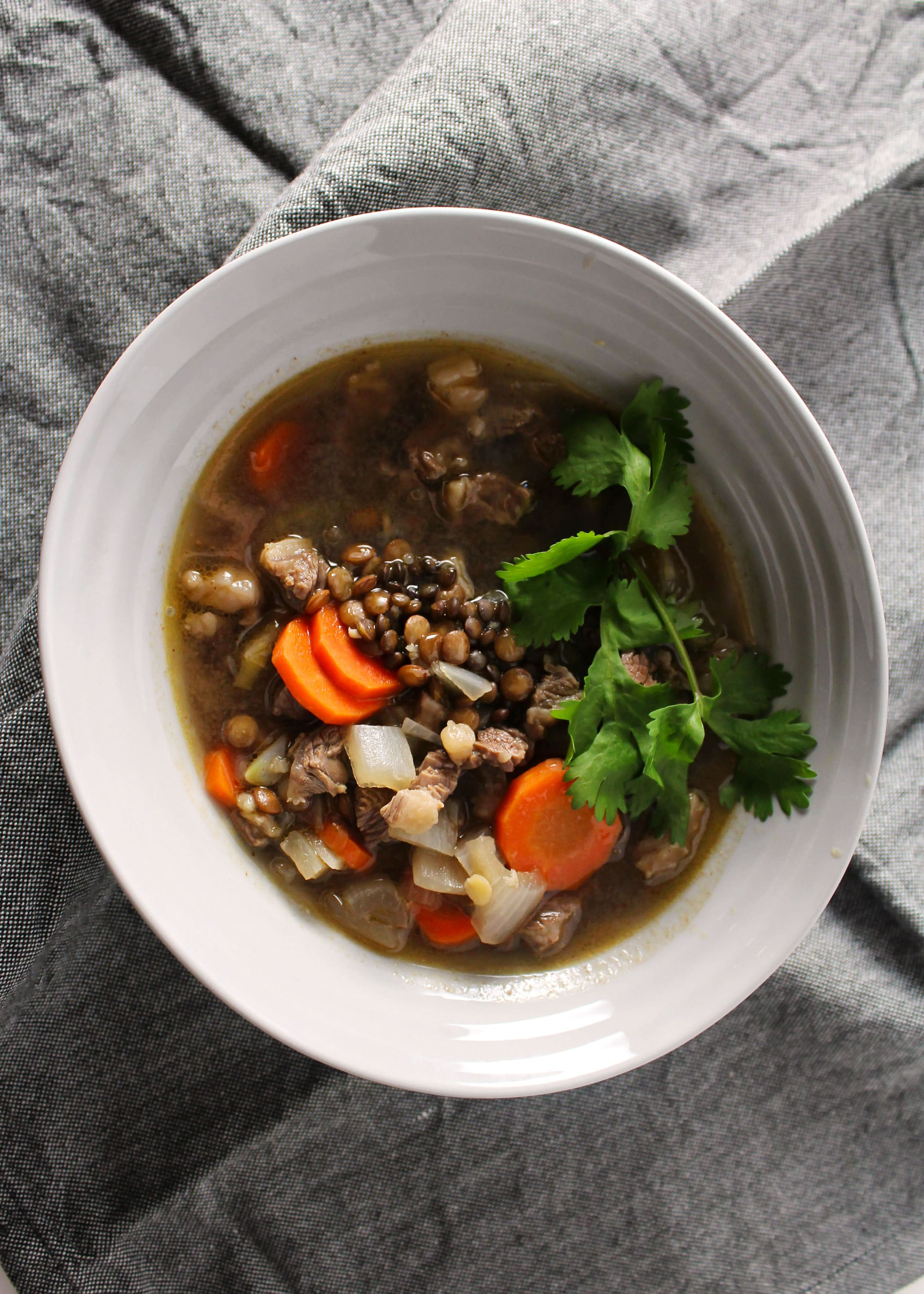 easy beef and lentil stew in gray bowl on linen napkin