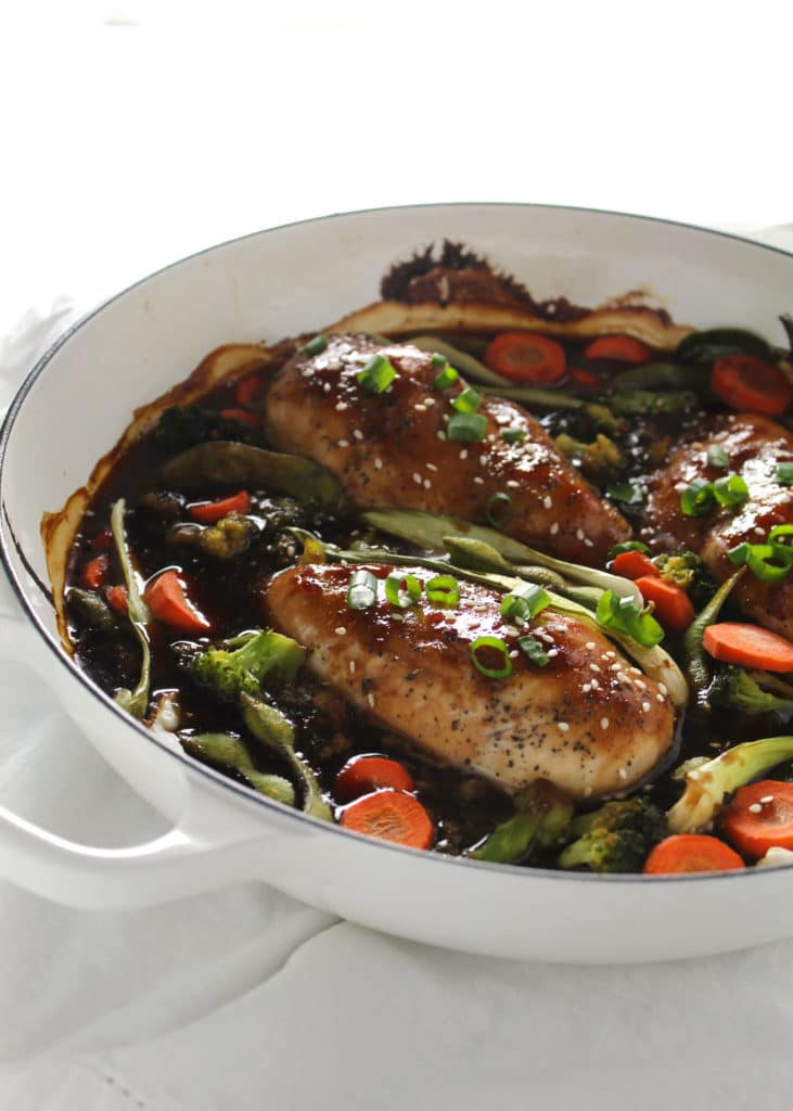 glazed chicken breast and vegetables in a white skillet