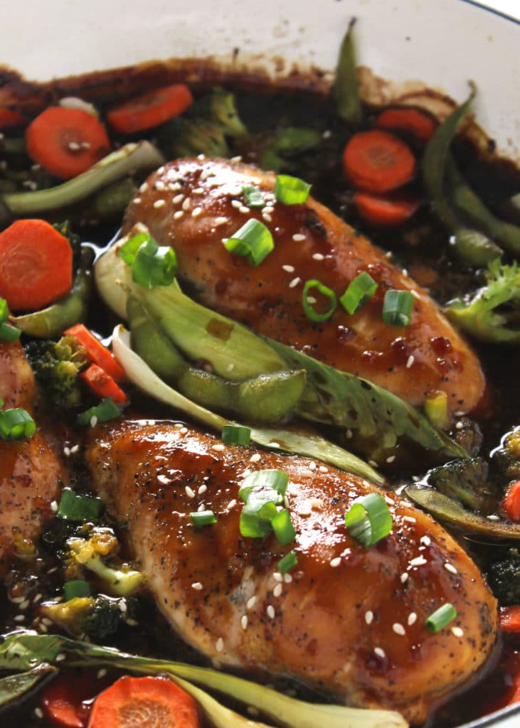 chicken teriyaki topped with sesame seeds and green onions surrounded by vegetables