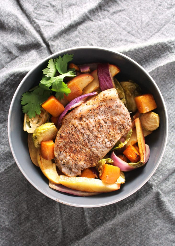 birds eye view of pork chop and vegetables in gray bowl