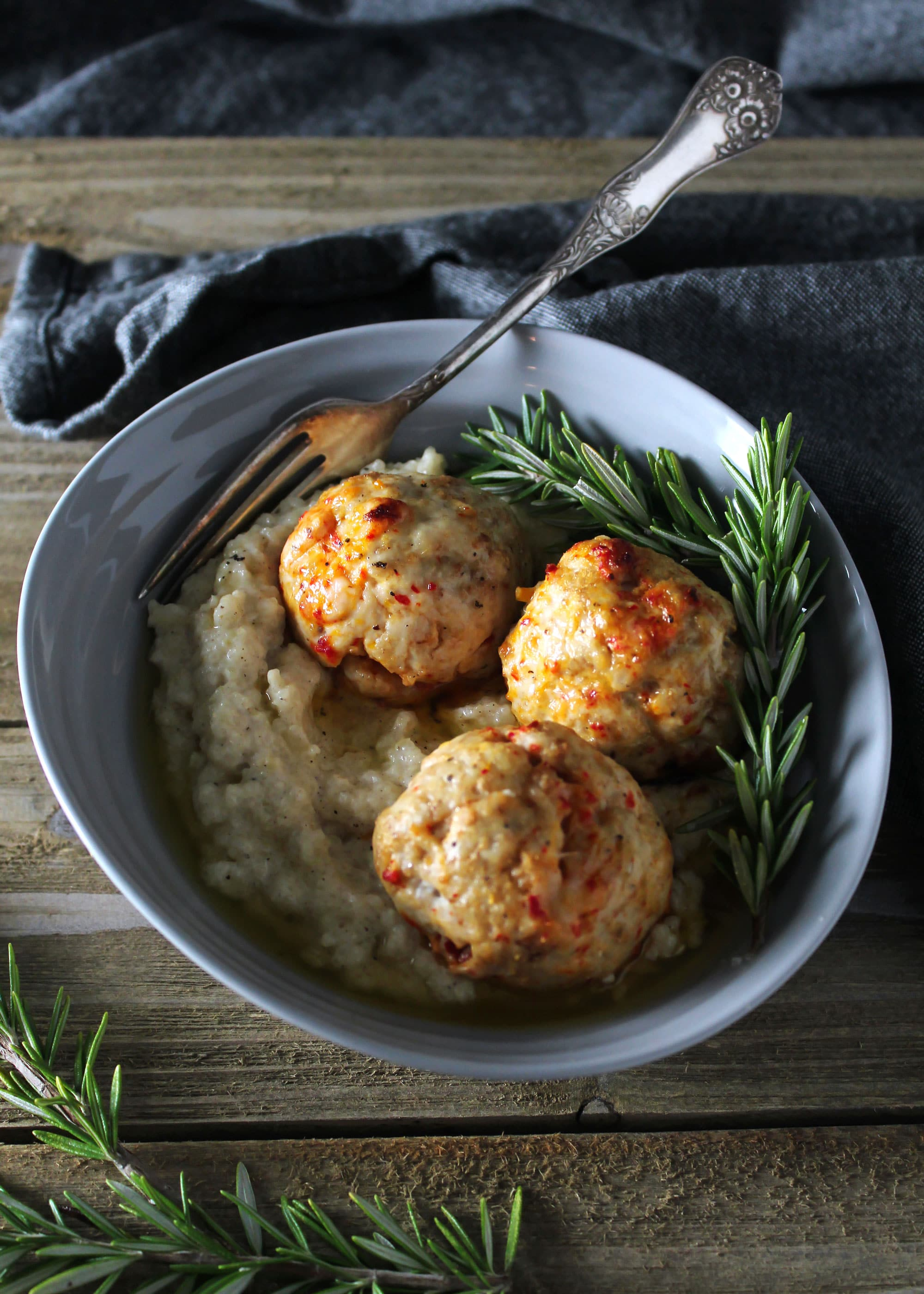 Pimento cheese meatballs on top of brown butter grits with rosemary sprigs in a gray bowl.