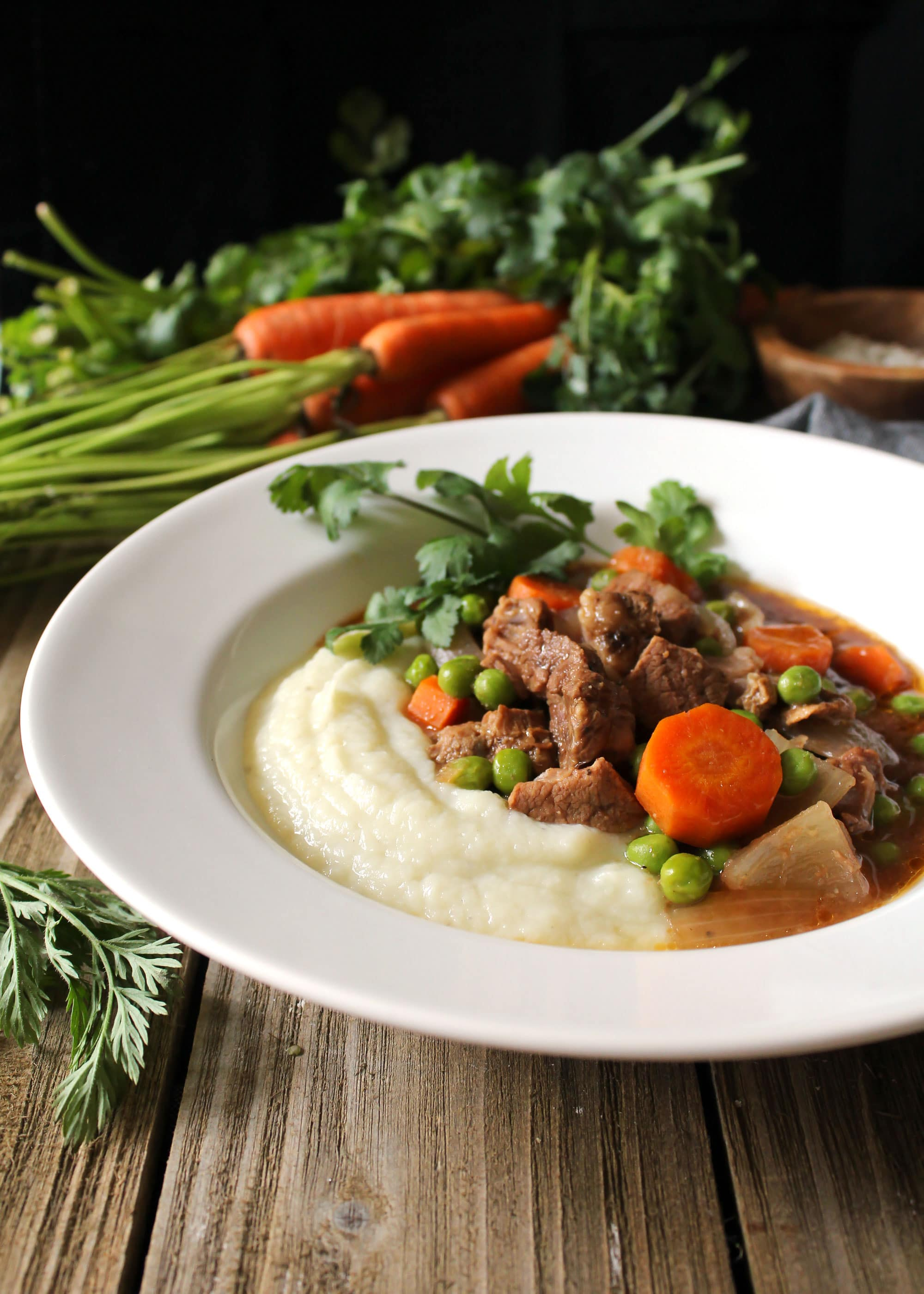 beef and vegetables over mashed cauliflower in white bowl