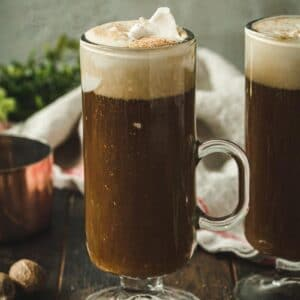 Vegan Irish coffee topped with coconut cream in a tall glass with a handle.