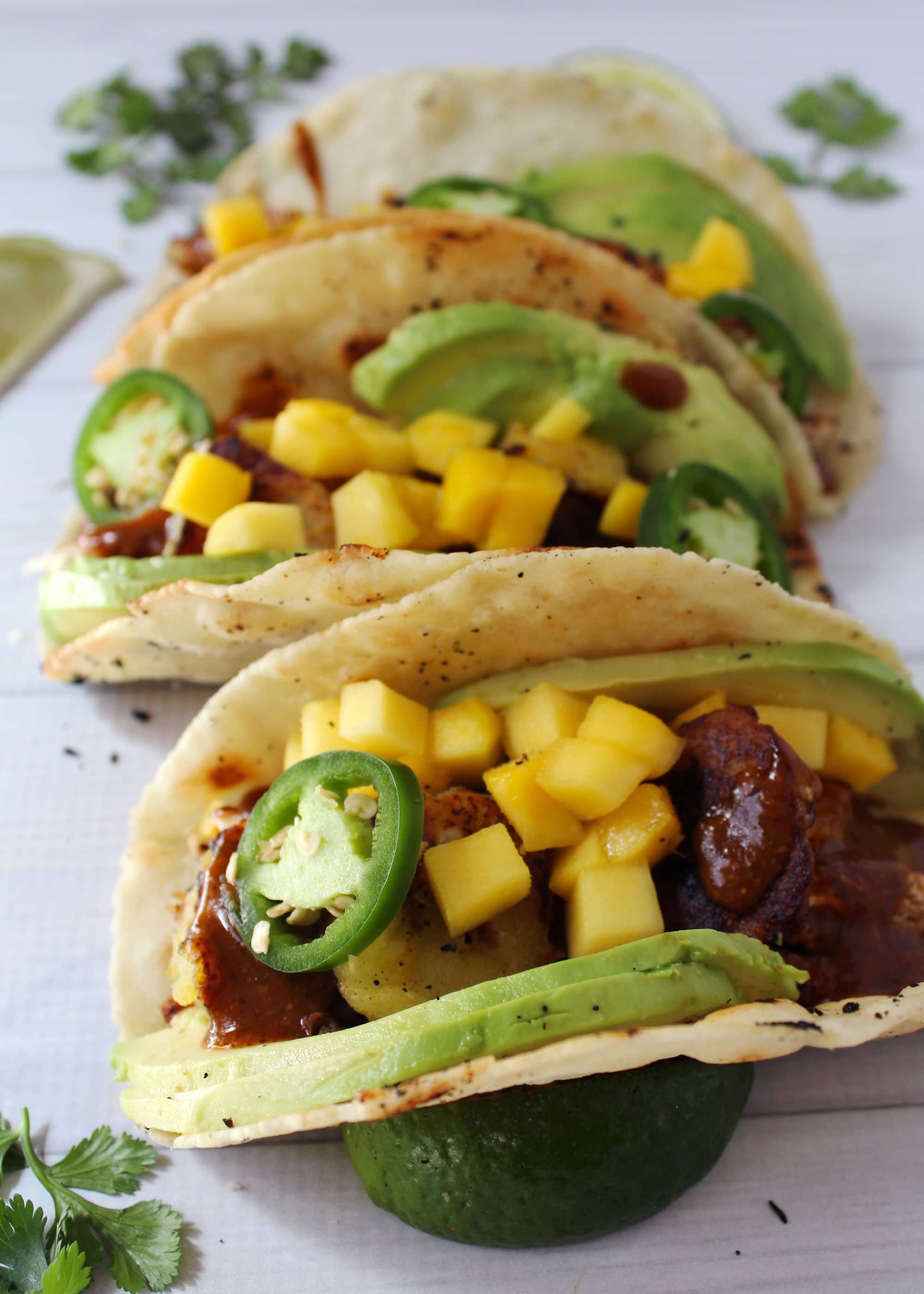 Jamaican jerk chicken tacos loaded with avocado and mango.
