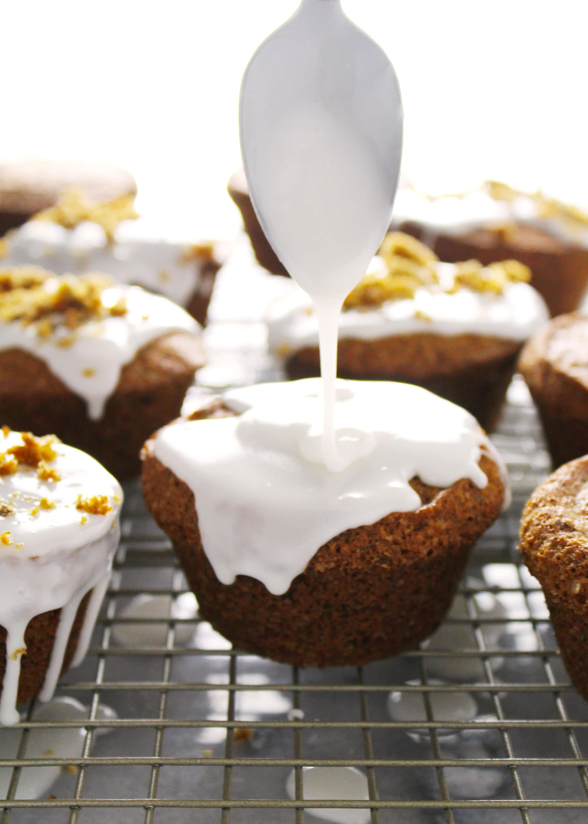 Maple spice orange muffin with a spoon drizzling icing on top.