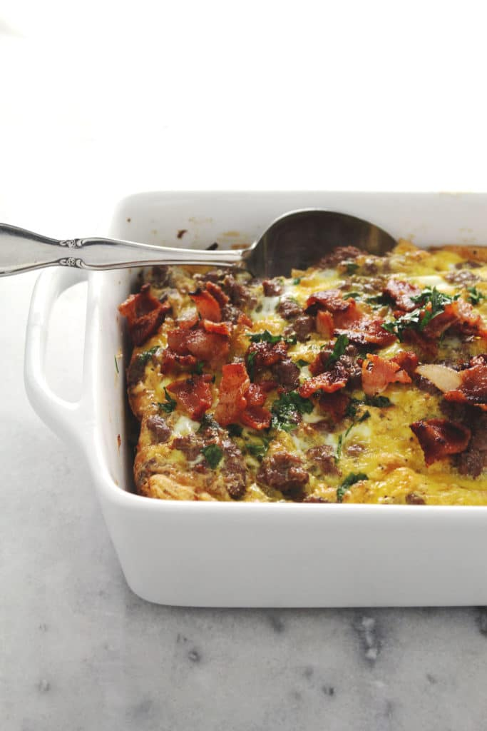side view of breakfast casserole topped with bacon and sausage