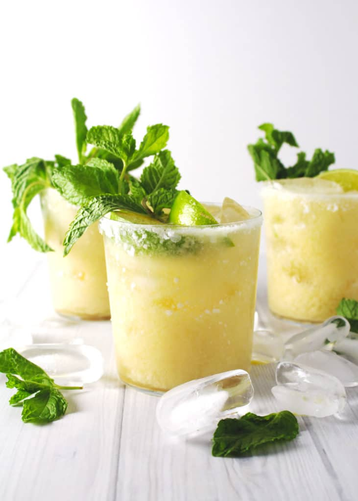 coconut and pineapple margaritas with salted rims and lime wedges