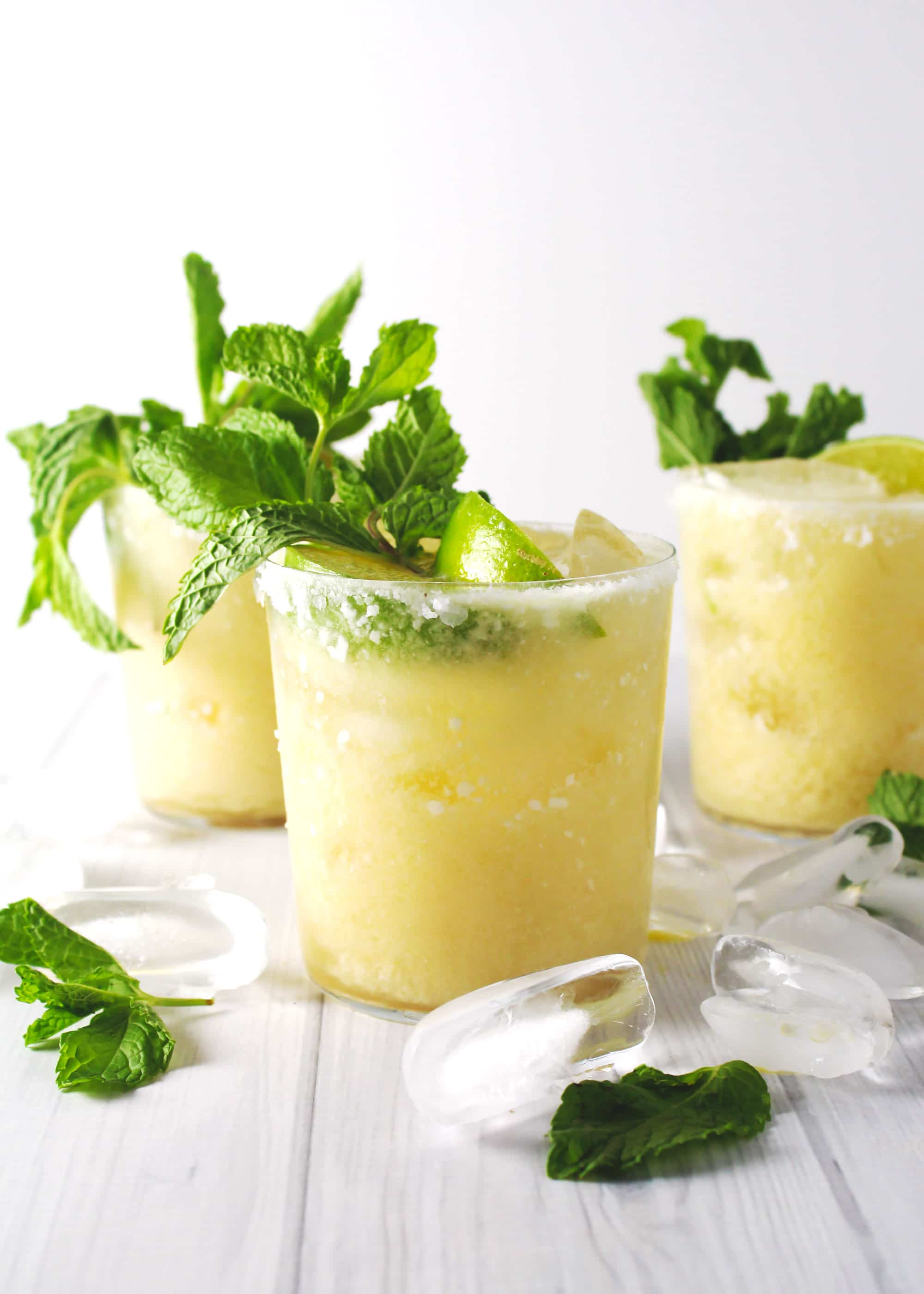 pineapple coconut margaritas with mint leaves on top and salted rims