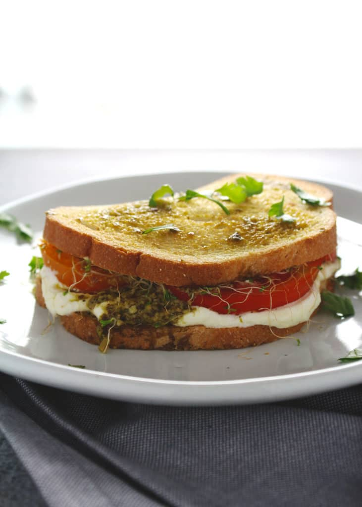 Enjoy this summer style sandwich with it's juicy tomatoes and creamy whipped feta spread topped with pesto sauce as you savor the warm days of the season | via @AimeeMarsLiving | #TomatoSandwich #WhippedFeta