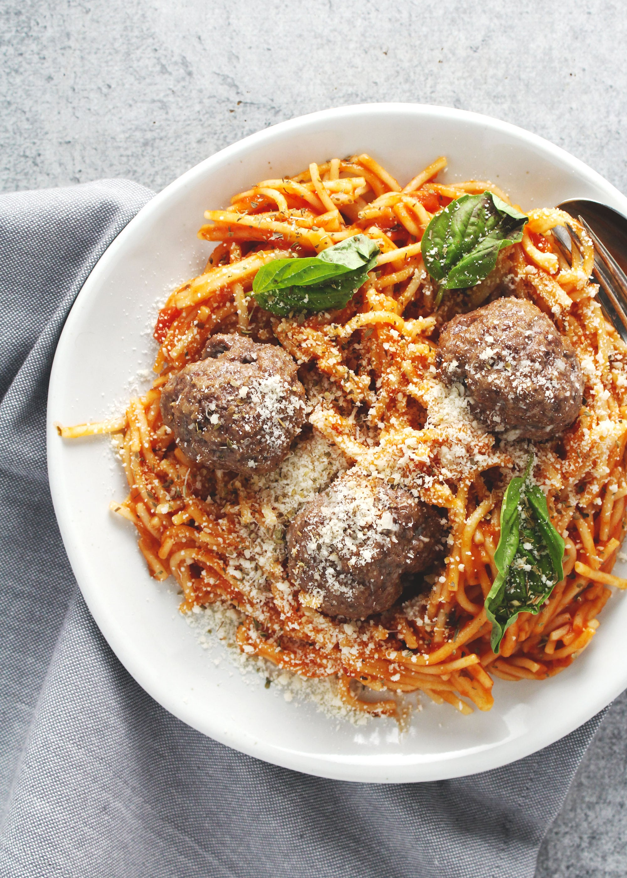 Spaghetti and meatballs with basil on top on a white plate.