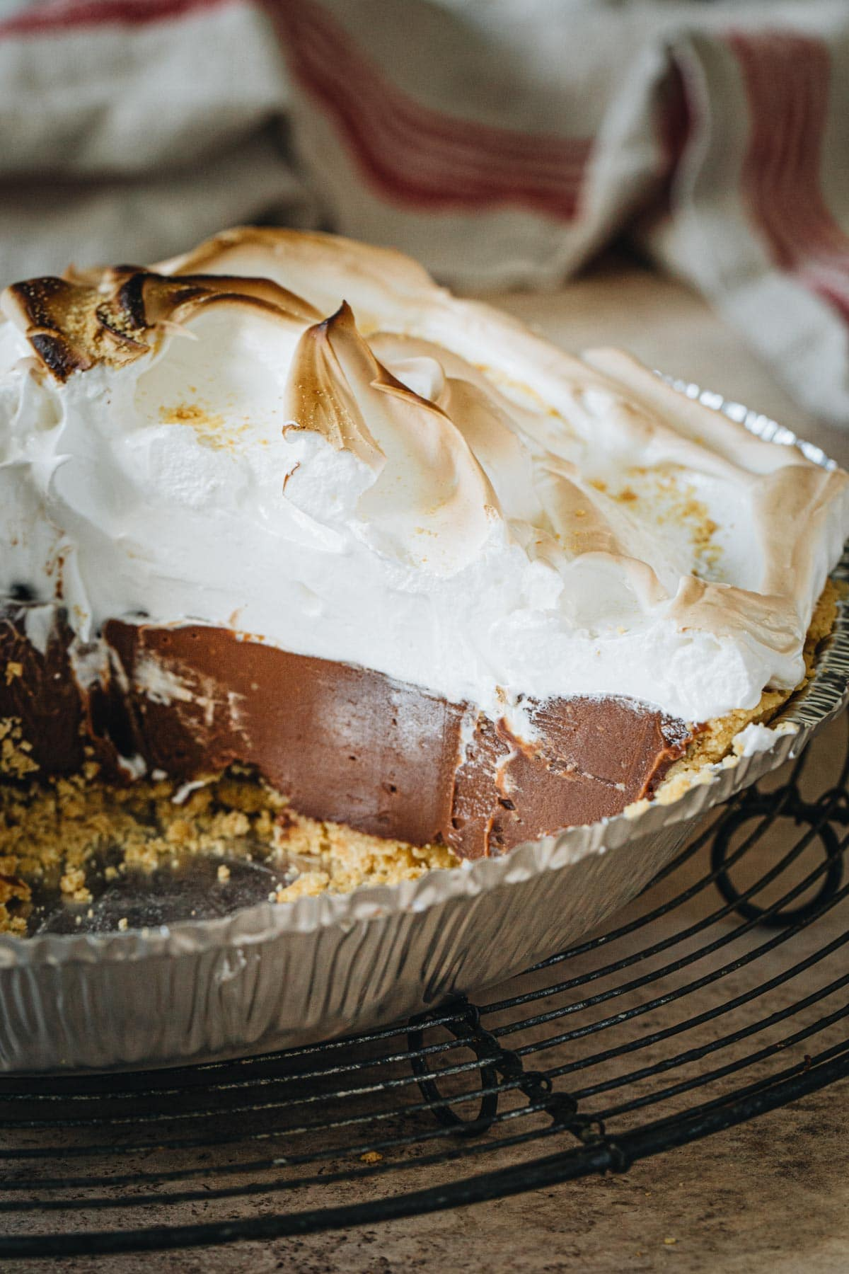 No-bake s'mores pie topped with marshmallow meringue in a metal pie plate.