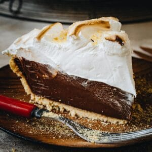 No-Bake S'mores Pie slice on a wooden plate.