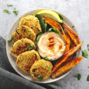 Chickpea zucchini fritters on a round plate with sweet potato wedges.